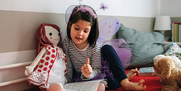 Girl disguised reading a book to her doll
